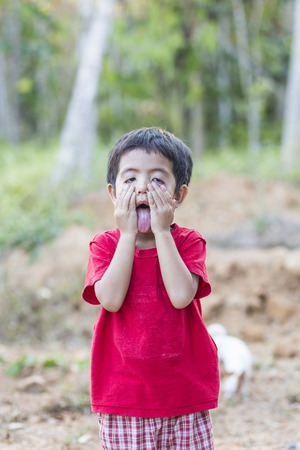 wry: Asian Thai little boy tongue and made a wry horrible face