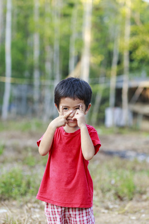 hands covering face: Portrait of happy cute Asian Thai little boy shy expression covering his face with hands outdoor