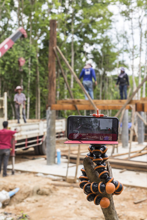 rigger: NAKHON SRI THAMMARAT, THAILAND - JUNE 7: Taking time lapse footage workers standing on wood beam and placing wood pillar by crane with smart phone on June 7, 2015 in Nakhon Sri Thammarat, Thailand.