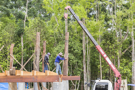 rigger: NAKHON SRI THAMMARAT, THAILAND - JUNE 7: Construction workers standing on wood beam on height and placing wood pillar on new house by crane on June 7, 2015 in Nakhon Sri Thammarat, Thailand.
