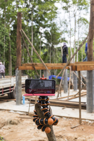 footage: NAKHON SRI THAMMARAT, THAILAND - JUNE 7: Taking time lapse footage workers standing on wood beam and placing wood pillar by crane with smart phone on June 7, 2015 in Nakhon Sri Thammarat, Thailand.