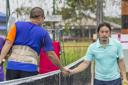 SURATTHANI, THAILAND - JUNE 20: Unidentifiled Thai tennis players shaking hands near the tennis net at Lang Suan tennis court on June 20, 2015 in Suratthani, Thailand.