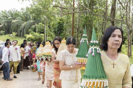 october 31: KRABI, THAILAND - OCTOBER 31: Asian Thai elderly women holding tray of gifts from the groom to the brides family on October 31, 2015 in Krabi, Thailand.
