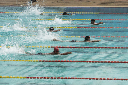 swimming race: NAKHON SI THAMMARAT, THAILAND - JANUARY 16: Unidentified young boys in goggles and cap swimming race action in pool lanes on January 16, 2016 in Nakhon Si Thammarat, Thailand. Editorial