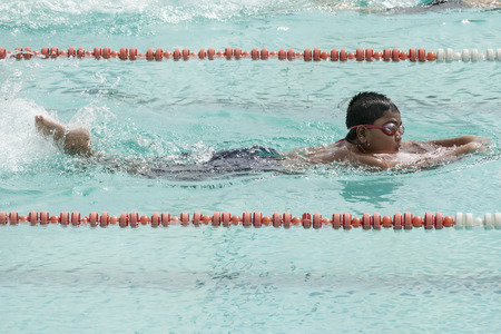 swimming race: NAKHON SI THAMMARAT, THAILAND - JANUARY 16: Unidentified young boy in goggles and cap swimming race closeup action in pool lanes on January 16, 2016 in Nakhon Si Thammarat, Thailand.
