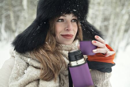 blondy: Beautiful blondy girl drink hot tea in a thermos in snowy forest Stock Photo