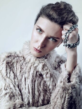 strict: Beauty portrait of a young white woman in fur with chain, look strict to camera