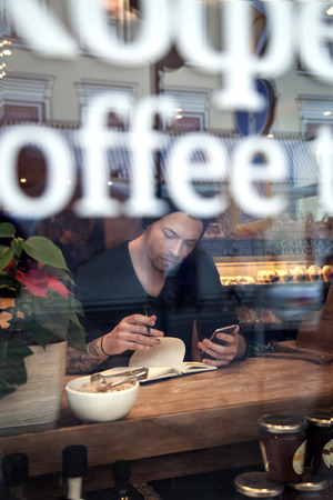 after hours: Potrrait of handsome white hipster man work in cafe, indoor vertical