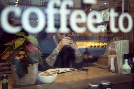 Ritratto di un bel bianco lavoro pantaloni a vita bassa uomo in caffè, focuse a portata di mano