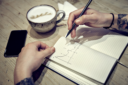 Close-up view of male hands with note book and coffee top view photo