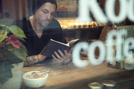 Portrait of handsome white hipster man read a book in cafe near window photo
