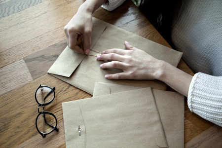 envelops: Close-up view of woman hands with hipster envelops cafe Stock Photo