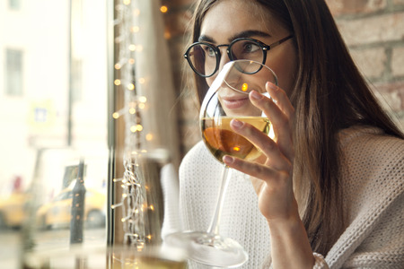 Woman drink white wine with friend in restaurant