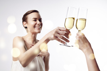 clang: Woman celebrating and says cheers at the party with a glass of champagne. Clang glasses together