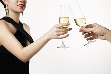 clang: Woman celebrating and clang glasses together with champagne. Party concept. White background Stock Photo