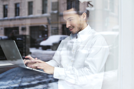 Young businessman or student sitting and working on the windowsill with open laptop on knees