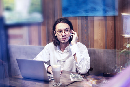 Attractive man in white shirt talking by phone and working on laptop in cafe or restaurant, having rest drinking coffee latte