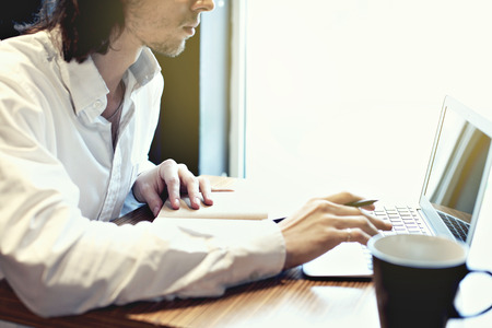 Young businessman or student, long hair, working writing on keyboard near window with open laptop