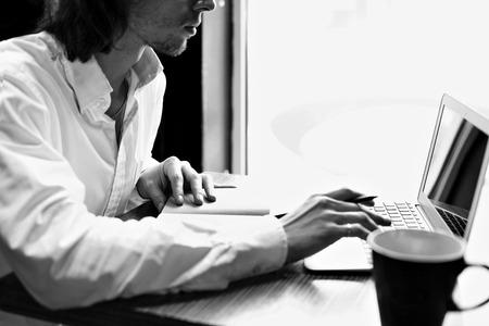 jeune homme d'affaires ou un étudiant assis et travailler près d'une fenêtre avec un ordinateur portable ouvert, noir et blanc