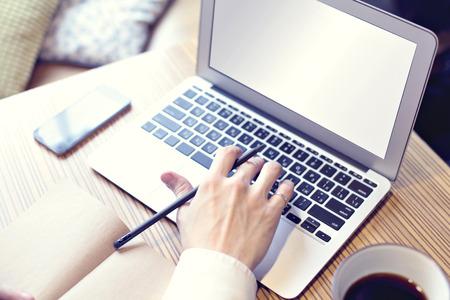 Ouvert ordinateur, homme d'affaires de boire du café et de travail sur ordinateur portable, téléphone mobile, l'écriture, close-up main droite