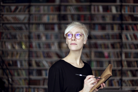 Portrait of woman with blonde hair and eyeglasses in a library, opened book. Hipster student. Education concept