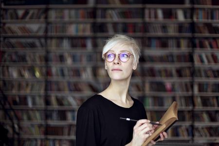 Ritratto di donna con i capelli biondi e gli occhiali in una libreria, libro aperto. studente Hipster. concetto di formazione