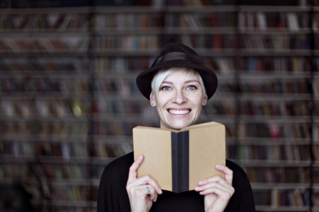 Portrait of woman in black hat with opened book smiling in a library, blonde hair. Hipster student girl