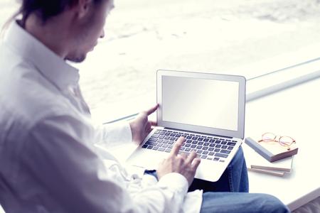 Hipster Handsome homme moderne entrepreneur travaillant à la maison utilisant un ordinateur portable près d'une fenêtre
