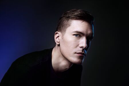 Beauty portrait of attractive hipster man with blue eyes on dark background