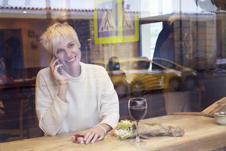 Beautiful blonde woman talking by mobile phone in cafe. Romantique breakfast for a date or St. Valentines Day. Present box and rose flowers.