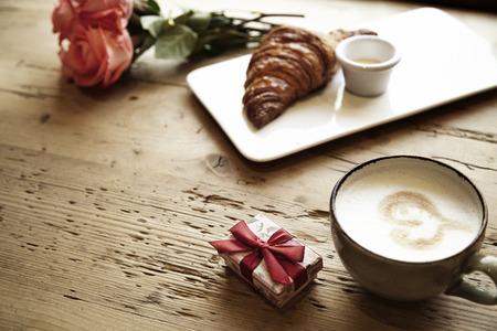 Croissant fresco da forno, caffè con il segno del cuore, fiori rosa su tavola di legno. Prima colazione romantica per San Valentino celebri concetto. Focus sulla scatola THW
