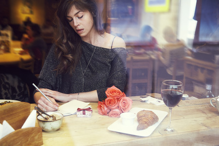 Beautiful european woman with long hair writing in notebook near window in cafe. Romantique breakfast, date or St. Valentines Day. Present box and rose flowers.