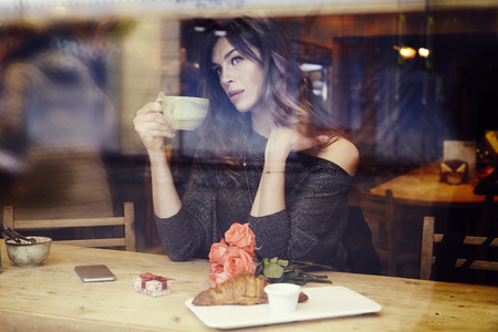 Beautiful caucasian woman with long hair near window in cafe. Romantique breakfast for a date or St. Valentines Day. Waiting someone, sad mood. Present box and rose flowers.