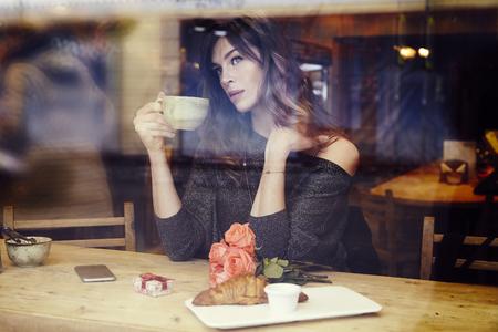 Bella donna caucasica con i capelli lunghi vicino alla finestra nel caffè. prima colazione Romantique per una data o il giorno di San Valentino. qualcuno in attesa, l'umore triste. Casella presente e fiori di rosa.
