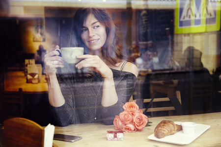 Bella donna caucasica con i capelli lunghi vicino alla finestra in caffè, festeggiare, box presente e fiori rosa. concetto di giorno di San Valentino o compleanno