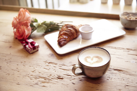 Romantic breakfast, Valentines Day celebrating. Present box, rose flowers, fresh croissant, coffee on wooden table. Focus on cup. Daylight from window.