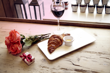 Romantic breakfast, Valentines Day celebrating. Present box, rose flowers, fresh croissant, wine on wooden table. Focus on flowers. Daylight from window. Stock Photo