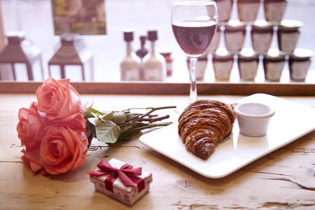 Romantic breakfast for Valentines Day celebrate. Present box, rose flowers, fresh croissant, wine on wooden table. Focus on croissant.