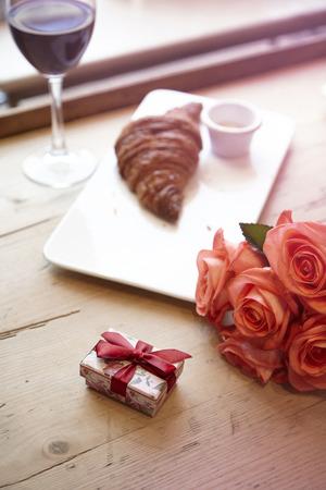 Prima colazione romantica per San Valentino celebri concetto. Croissant fresco da forno, vino rosso, fiori rosa su tavola di legno.