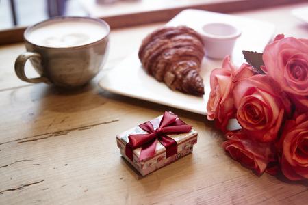 Prima colazione romantica per San Valentino festeggiare. scatola di Presente, fiori di rosa, croissant coffeeon tavolo di legno fresco.