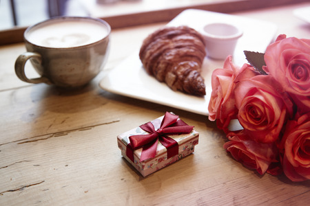 Romantic breakfast for Valentines Day celebrate. Present box, rose flowers, fresh croissant coffeeon wooden table.