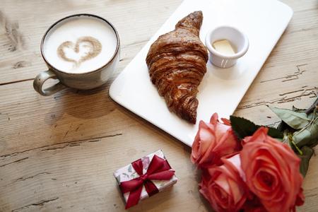 Croissant fresco da forno, caffè con il segno del cuore, fiori rosa su tavola di legno. Prima colazione romantica per San Valentino celebri concetto