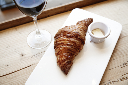 Fresh bakery croissant and glass of red wine in wooden table. City cafe daylight near window