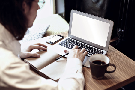 Man in white shirt working on portable computer and drinking coffee in a cafe or coworking. Focus on keyboard and phone Stock Photo