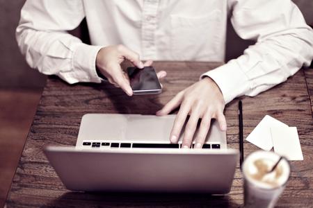 L'uomo in camicia bianca di lavoro sul computer portatile e bere latte in un bar o coworking. Concentrarsi sulla mano e la tastiera del ragazzo