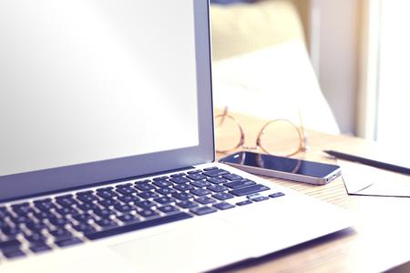 computer portatile aperto con spazio schermo in bianco per il layout design. Focuse su angolo dello schermo. telefono cellulare, occhiali. Affari ancora concetto di vita