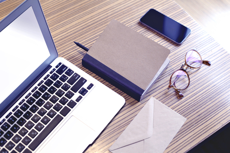 Opened laptop computer with blank screen space for design layout, mobile phone, glasses, envelope. Business still life concept