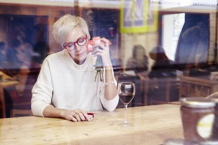 Blonde woman with short hair and eye glasses sitting in a cafe or restaurant near window. Romantic mood, present and flowers in hand. Javascript:void(0)t. Valentines day concept Stock Photo