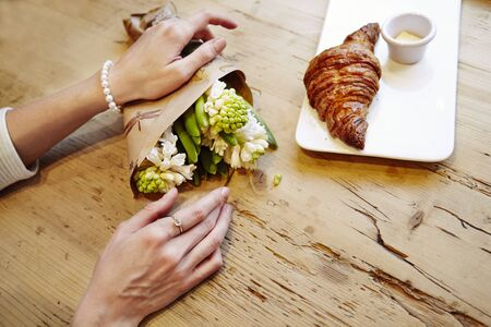 Woman hands with ring on finger, hyacinth bouquet flowers, romantic date in cafe, breakfast with croissant and coffee. St. Valentines day