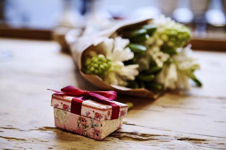 Petite boîte présente mignon avec un arc à la table en bois, fleurs rose derrière. Le concept de la Saint-Valentin jour.